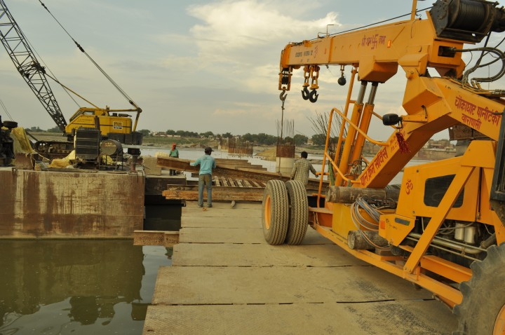 A crain dismantles the Samne ghat construction bridge for the monsoon season in Varanasi.