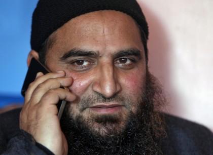 Masarat Alam Bhat, a Kashmiri separatist leader, speaks on his mobile phone at his residence in Srinagar